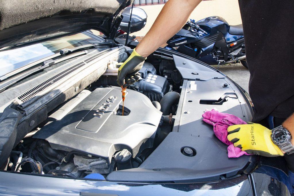 Mécanicien automobile qui est en train de travailler au niveau du moteur d'une voiture