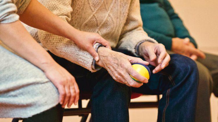 Personne qui tient le poignet d'une personne âgée