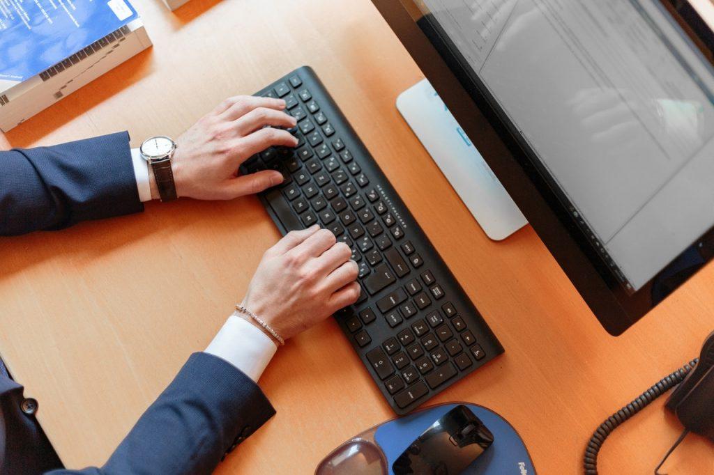 personne en costume qui tape sur un ordinateur de bureau