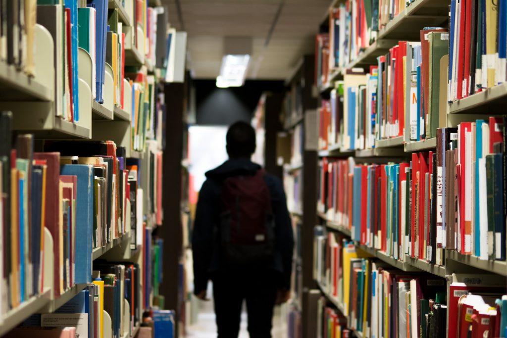bibliothèque avec homme de dos au milieu